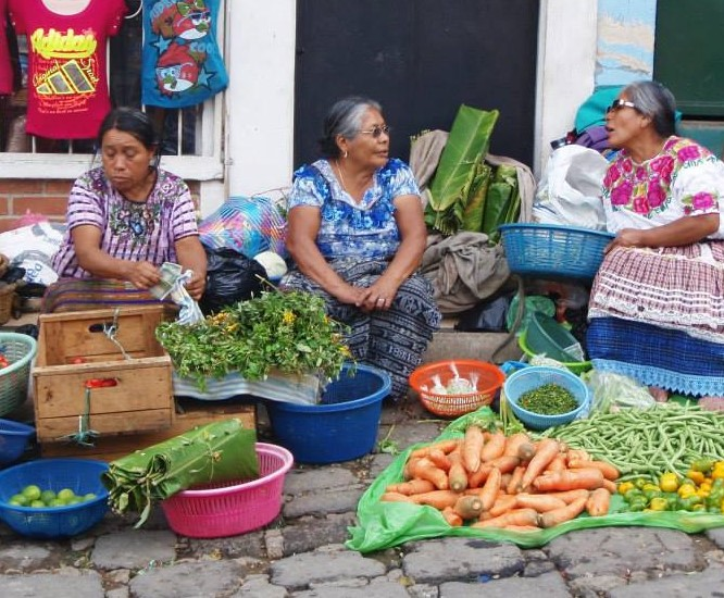 Ladies in traditional Mayan clothing selling fruit.